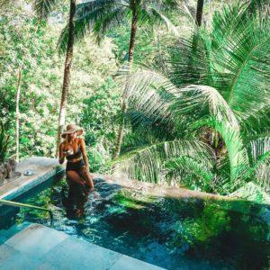 : influencer woman in a bikini in a bali pool