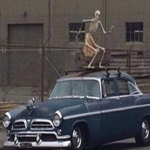 skeleton dancing on top of a hearse